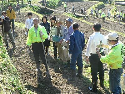 川村委員長による現地での種まきの解説